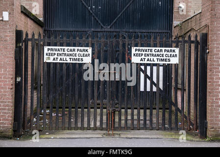 Security Gates with signs saying 'Private car park. Keep entrance clear at all times'. - Stock Photo