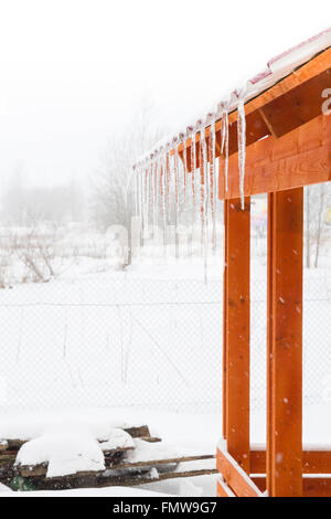 Icicles hanging from the roof of the gazebo in the countryside - Stock Photo