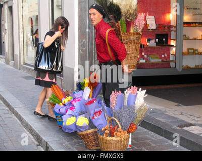 A woman purchasing flowers from a street vendor. - Stock Photo