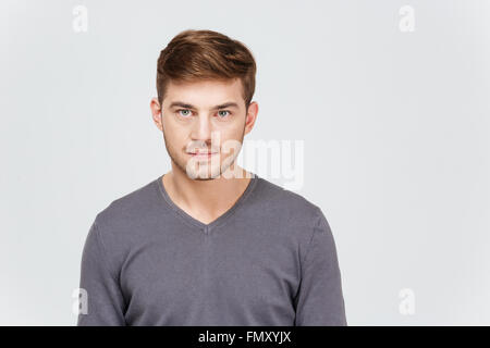 Portrait of serious handsome young man in grey pullover over white background - Stock Photo