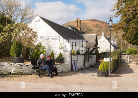 middle aged couple enjoying early spring sunshine outside the gift shop in Luss, Loch Lomond, Scotland, UK - Stock Photo