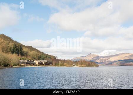 Lodge on Loch Lomond Hotel, Luss, Loch Lomond, Scotland in March with a snow capped Ben Lomond - Stock Photo
