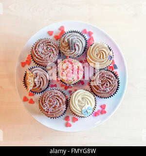 Top down above view on eight deliciously sweet cupcakes covered with creamed chocolate, vanilla and various other - Stock Photo