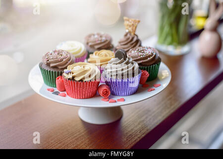 Eight deliciously sweet cupcakes covered with creamed chocolate, vanilla and various other garnishments alongside - Stock Photo