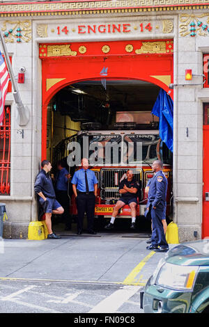 NEW YORK CITY - OCTOBER 8, 2014: New York fire fighters taking a break sitting on the truck at engine 14 in East - Stock Photo