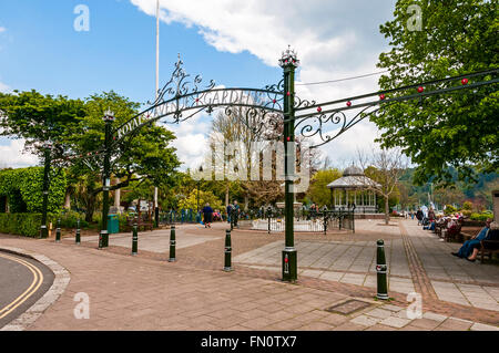 The cast iron posts and bollards at the entrance to the gardens frame people passing through or just relaxing on - Stock Photo