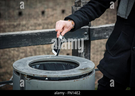 Unrecognizable man throwing his cell phone in trash bin in the street - Stock Photo