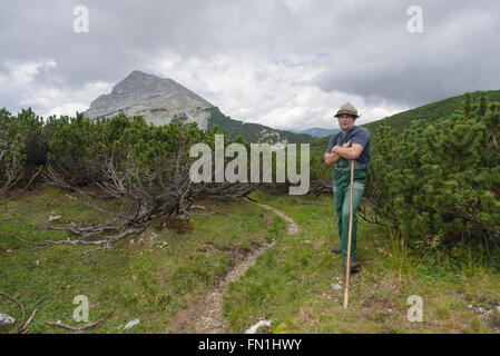 Portrait of a mountain farmer between mountain pines in front of the summit of Mount Guffert, Rofan, Tirol, Austria - Stock Photo