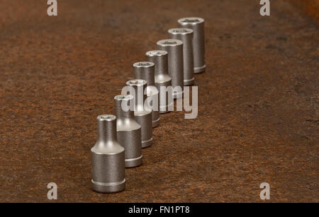 Closeup on socket wrench parts placed on at rusty steel plate - Stock Photo