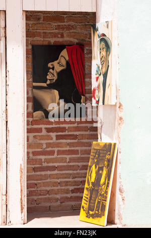 Paintings on display in doorway at Trinidad, Cuba, West Indies, Caribbean, Central America in March - Stock Photo