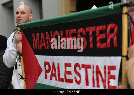 Manchester, UK. 13th March, 2016. A campaigner holding a flag which has 'Manchester Palestine' written on it in - Stock Photo