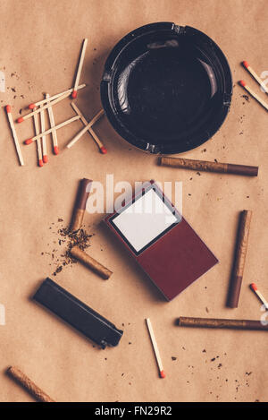 Passionate smoker flat lay table top view arrangement, warm retro toned image of ashtray, cigarettes, matches and - Stock Photo