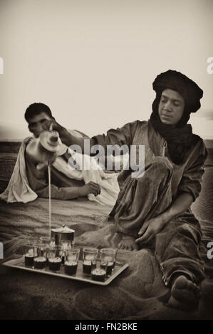 ZAGORA, MOROCCO - JUNE 14: Unidentified berber natives preparing tea over sand on June 14, 2010, Zagora, Morocco - Stock Photo