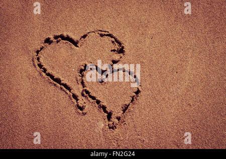 hearts drown into sand on beach - Stock Photo