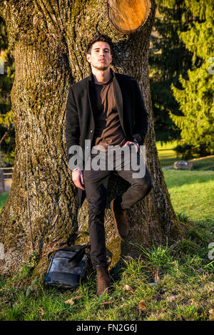 Handsome young man leaning against tree, looking at camera, in a sunny day wearing a black coat - Stock Photo