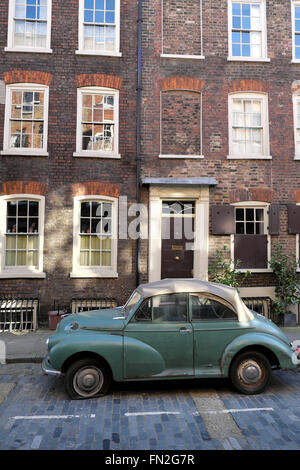 Morris Minor car with a flat tire parked on Elder Street in Spitalfields, East London E1  KATHY DEWITT - Stock Photo