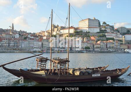 Rabelo boat, used to transport Port Wine, on the Douro river next to Dom Luis bridge in Porto, Portugal - Stock Photo