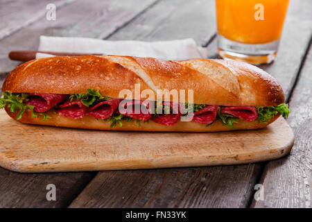 baguette sandwich with salami and herbs on a wooden surface - Stock Photo