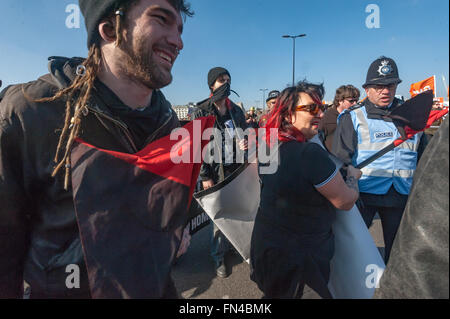 London, UK. 13th March, 2016. Police attempt to persuade Class War and other anarchists to stop blocking traffic - Stock Photo