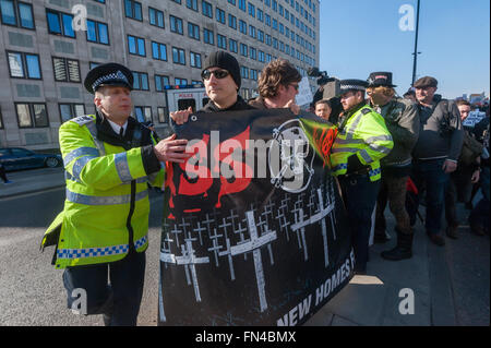 London, UK. 13th March, 2016. Class War ignore police attempts to persuade them and other anarchists to stop blocking - Stock Photo