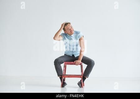 young man brutal man in a shirt with short sleeves sitting on red chair his fists clenched - Office Chair For Short Person
