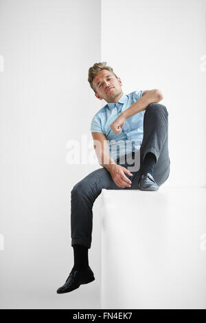 Brutal man with a small beard sitting on a wide windowsill , a hand on his knee , wearing a blue short-sleeved shirt - Stock Photo