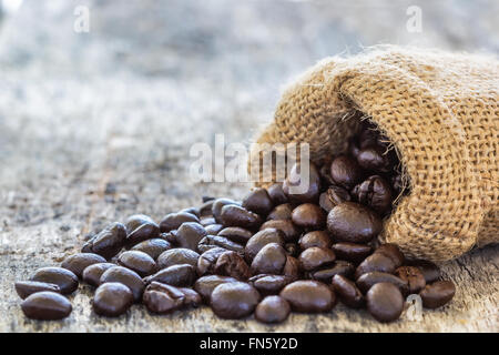 Close up shot Coffee beans poured from the sack on old wooden table - Stock Photo