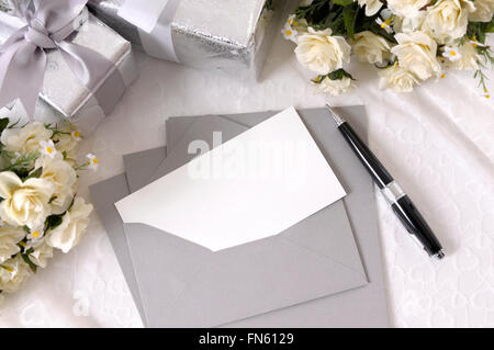 Writing paper or wedding invitation with envelope laid on bridal lace with several wedding gifts and white rose - Stock Photo