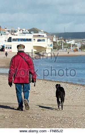 Older man walking his dog along the beach at Weymouth, Dorset, England - Stock Photo