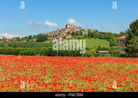 Rural field of red poppies under blue sky as small town on the hill on background in Piedmont, Northern Italy.