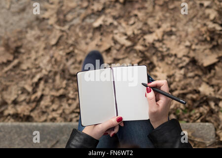 Top view image of open pad in feamle hands with pen sitting on stairs in the park. Blank sheets of small notebook - Stock Photo