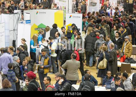 Migrants and refugees walk around stands offering jobs and education at a job fair for refugees in Berlin, 29 February - Stock Photo