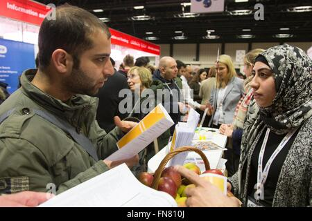 migrants and refugees walk around stands offering jobs and education stock photo 99136896 alamy. Black Bedroom Furniture Sets. Home Design Ideas