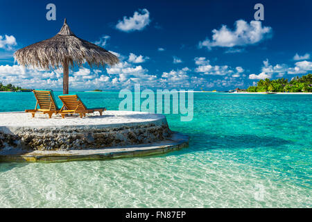 Two beach chairs under umbrella with ocean view in tropical Maldives - Stock Photo