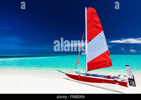 Sailing boat with red sail on a beach of deserted tropical island with shallow blue water - Stock Photo