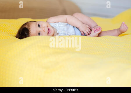 Baby lying on a bed - Stock Photo