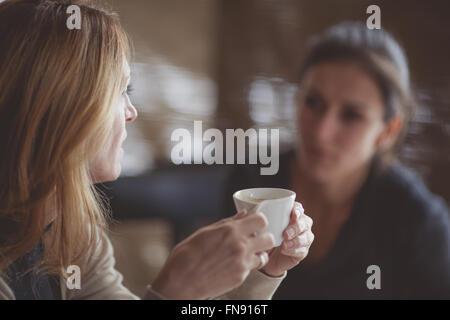 Two women drinking coffee - Stock Photo