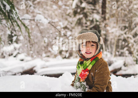 Smiling boy in forest in winter - Stock Photo