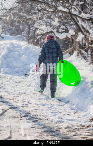 Boy walking in snow carrying sledge - Stock Photo