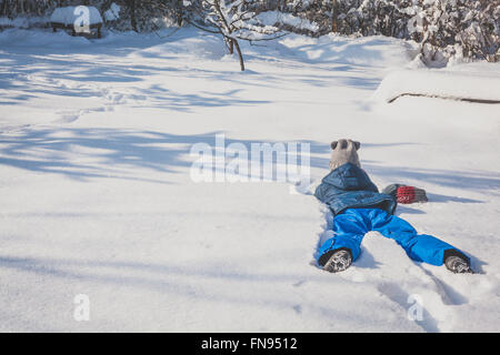Girl lying on her front in the snow - Stock Photo