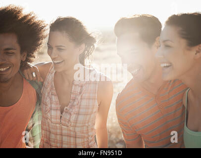 A group of friends, men and women, on the open road, walking and talking. - Stock Photo
