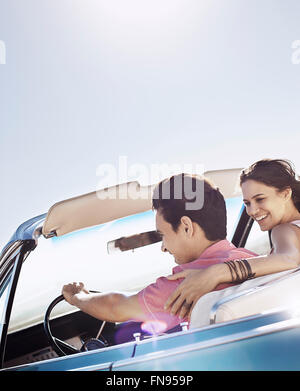 A young couple, man and woman in a pale blue convertible on the open road - Stock Photo
