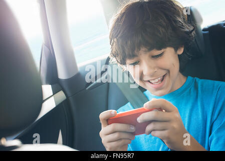 A boy sitting in a car using a handheld games tablet. - Stock Photo
