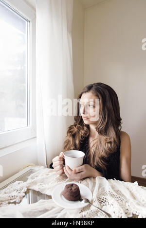 Young woman sitting with cup of tea and chocolate dessert - Stock Photo