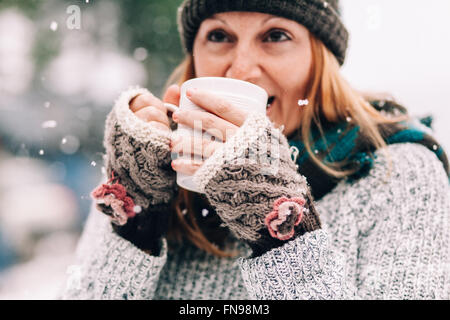 Woman standing in snow holding hot drink - Stock Photo