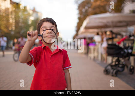 Young boy smiling through magnifying glass, sofia, bulgaria - Stock Photo
