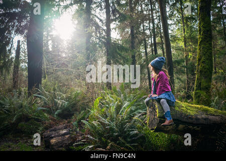 Young girl sitting on moss covered tree in the forest - Stock Photo