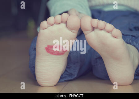 Lipstick kiss on toddler's foot - Stock Photo