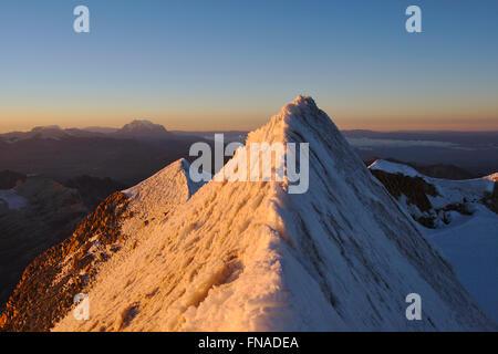 Summit ridge of Huayna Potosi in the Cordillera Real, sunrise, Illimani in the distance, Bolivia - Stock Photo