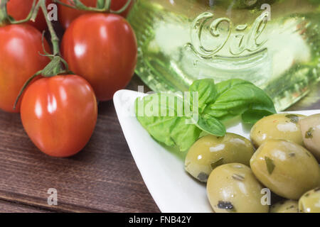 White bowl with marinated green olives is placed on a wooden desk. Tomatoes are lying on a desk of olive wood. - Stock Photo